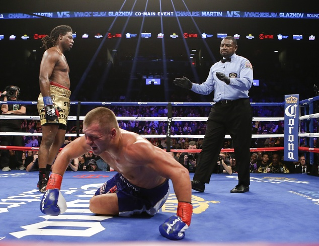 Vyacheslav Glazkov, of Ukraine, center, gets up as Charles Martin, left, walks away during the third round of a IBF heavyweight title boxing match Saturday, Jan. 16, 2016, in New York. Martin stopped Glazkov in the third round. (AP Photo/Frank Franklin II)