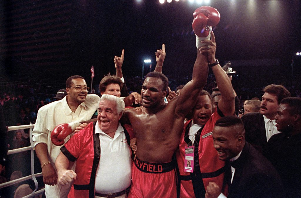 "FILE - In this Oct. 25, 1990, file photo, the new world heavyweight champion Evander Holyfield is supported by his trainers Lou Duva, left, and George Benton, right, after his third round knock-out of James ""Buster"" Douglas at the Mirage Hotel in Las Vegas, Nev. Duva, the Boxing Hall of Famer trainer who handled the careers of 19 champions including heavyweight titlist Evander Holyfield, died Wednesday, March 8, 2017, of of natural causes at a hospital in Paterson, N.J., where he lived, his son Dino said. He was 94. (AP Photo/ Douglas C. Pizac, File)"